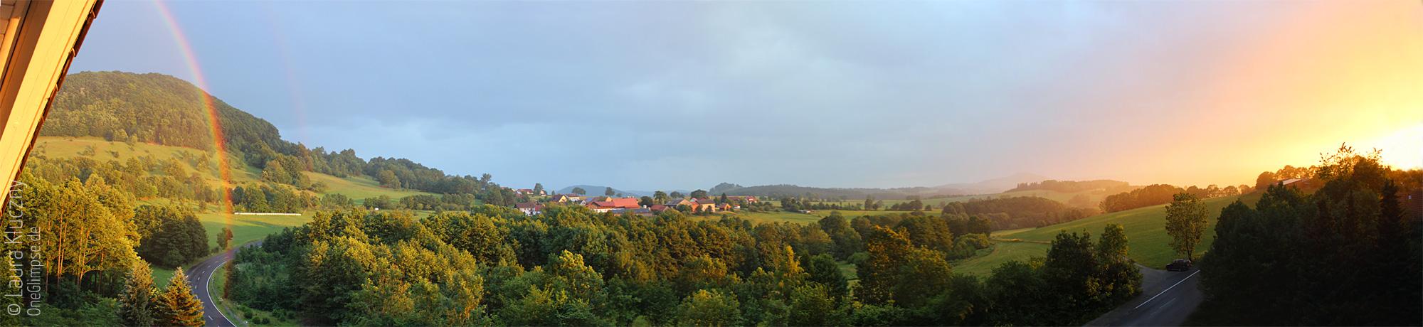 Rhön: Ausblick vom Hotel-Balkon mit Regen, Sonnenuntergang und Regenbogen/Panorama